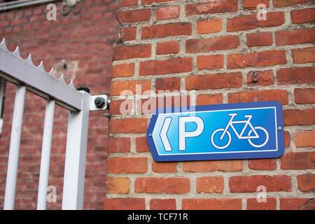 Parking vélo bleu brun rouge signe sur mur de briques à côté de clôture blanche. Banque D'Images