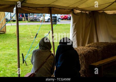 En couple, les deux portant des hauts hoodie humide, assis dans l'embrasure d'une tente lors d'un événement, à l'abri de la pluie. Sur l'épaule de vue.