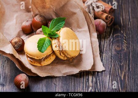 Le caramel et la cannelle macarons à la noisette et à la menthe sur la table en bois brun. Selective focus Banque D'Images