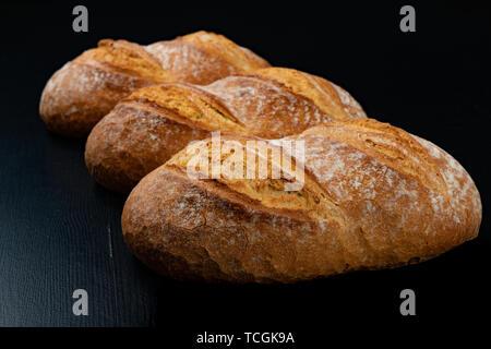 Un pain savoureux fraîchement cuits sur un tableau sombre. De délicieux produits de boulangerie tout droit de la boulangerie. Fond noir.