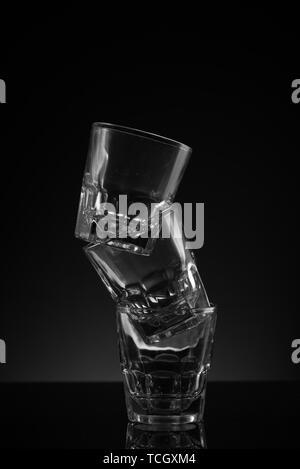 Verre clair empilés verres fond noir surface réfléchissante et arrangement maladroit