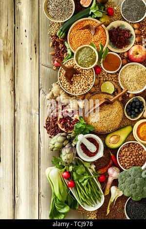 Assortiment nutritifs des fruits et légumes à proximité de plusieurs bols de riz sur fond de bois rustique Banque D'Images