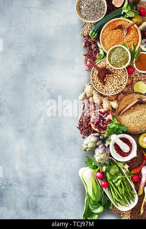 La frontière de l'alimentation avec un grand assortiment de fruits frais, d'épices, herbes et légumes sur une ardoise avec fond texturé copy space Banque D'Images