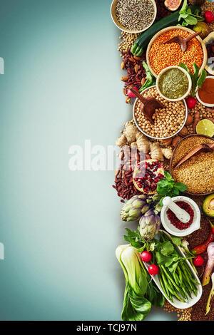 Grand choix de légumes frais, de fruits, de graines et d'épices dans un aliment conceptuel à la frontière d'une saine alimentation et la nutrition sur un fond bleu avec v Banque D'Images