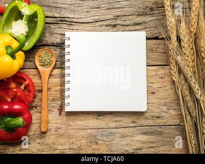 Mise à plat de cuisson et ustensiles de cuisine livre de recettes avec des herbes et des poivrons colorés sur fond de bois. Vue de dessus avec copie espace alimentaire une recette. Banque D'Images