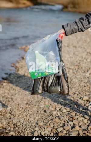 Les déchets dans la nature, le nettoyage de l'environnement au printemps sur la rivière à partir de la poubelle une femme en bleu à usage unique en latex à grand bleu en mitaines Banque D'Images