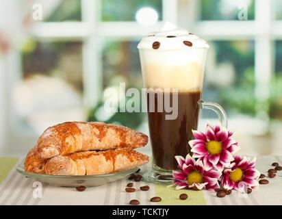 Verre de cocktail café et soucoupe avec des bagels sur la table Banque D'Images