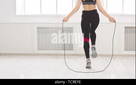 Femme méconnaissable sautez par-dessus le la corde à sauter en studio Banque D'Images