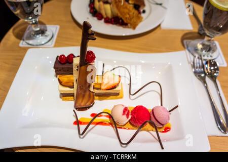 Délicieux des couches de glace de couleur crème avec des fraises fraîches et les cerises, le chocolat et les spirales du violon plaque blanche, selective focus Banque D'Images