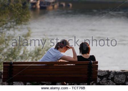 Les jeunes femmes sur un banc de parc en profitant de la vue sur le lac leur temps ensemble Banque D'Images