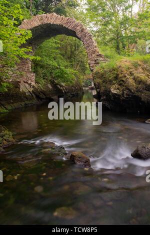 Vue de l'ancien pont de Cromwell à Kenmare, comté de Kerry, Irlande, prises à partir de l'amont sur une longue exposition à lisser l'eau, personne au