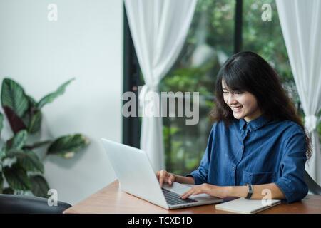Asian woman using laptop computer près de fenêtre à cafe restaurant,mode de vie,à l'aide d'âge numérique Technolgy concept,l'espace de travail co Banque D'Images