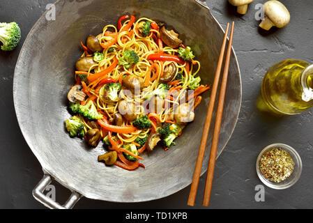 Faire sauter les nouilles avec les légumes dans le wok casserole sur fond noir en noir. Haut de la vue, télévision lay Banque D'Images
