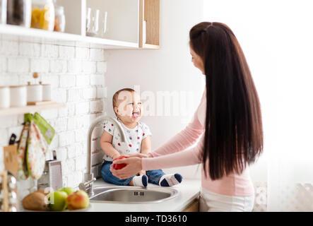 Adorable baby sitting on table dans la cuisine pendant que maman lave-apple Banque D'Images