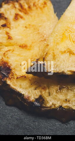 Les tranches d'ananas grillées close up sur fond noir Banque D'Images
