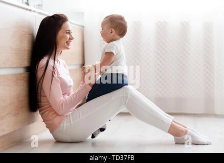 Belle mère jouer avec bébé adorable dans la cuisine Banque D'Images