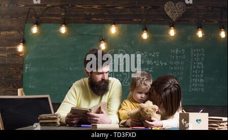 Père Fils, enseigne la lecture de livre, alors que mère jouer avec toy, tableau sur l'arrière-plan. Famille se soucie de l'éducation de leur petit fils smart. Garçon li Banque D'Images