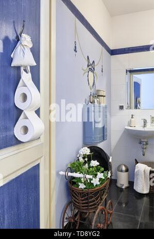 Fleurs blanches en poussette poupée en osier à l'entrée Salle de bains Banque D'Images