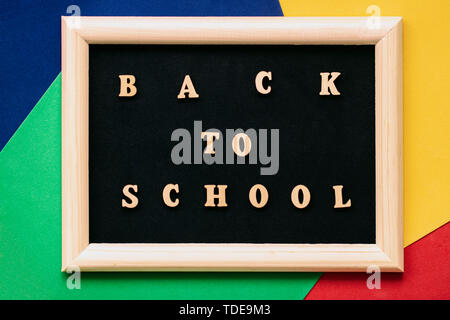 Retour à l'école texte écrit des lettres en bois noir sur tableau noir dans l'image. Concept de l'éducation, à l'école, de retourner à l'école. Arrière-plan coloré Banque D'Images