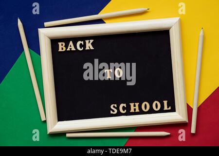 Retour au texte de l'école en bois noir et crayons sur tableau noir dans cadre en bois. Concept de l'éducation, à l'école, de retourner à l'école. Arrière-plan coloré Banque D'Images