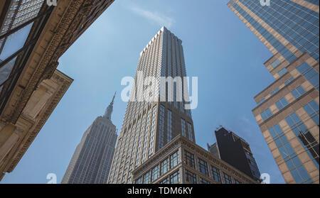 New York, Manhattan centre commercial. Gratte-ciel et l'Empire state building en perspective contre le fond de ciel bleu, low angle view, printemps sunn