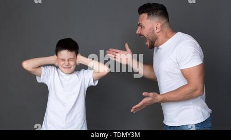 Père furieux de crier sur son fils, peur enfant fermer les yeux et les oreilles Banque D'Images