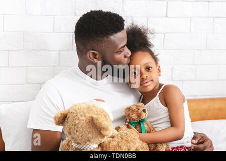 Son père africain soins adorable petite fille en front Banque D'Images