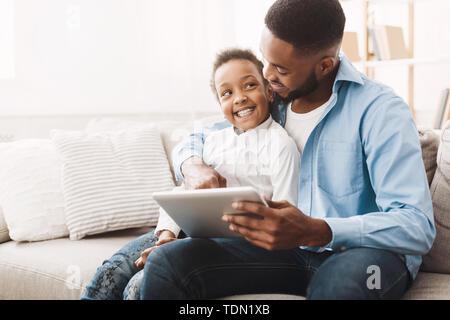 Père et fille africaine jouant sur Tablet