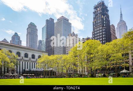 New York, Manhattan, vue sur l'horizon de Bryant Park, le printemps. Gratte-ciel, les gens se détendre, vert pelouse et arbres, fond de ciel bleu clair Banque D'Images