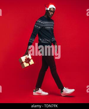 Young African man wearing santa hat sautant avec boîte-cadeau sur fond rouge. Beau black avec un cadeau de Noël sur fond rouge. Banque D'Images