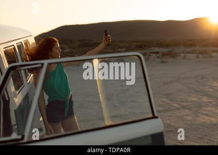 Belle jeune femme en tenant près de selfies camper van at beach Banque D'Images