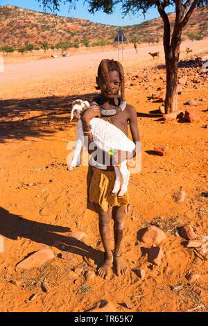 Jeune fille Himba portant un agneau, Namibie Banque D'Images