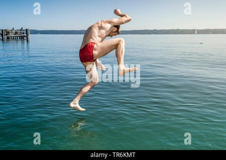 Jeune homme en rouge les lignes de baignade dans le lac juming Le Lac de Starnberg, Allemagne, Bavière Banque D'Images