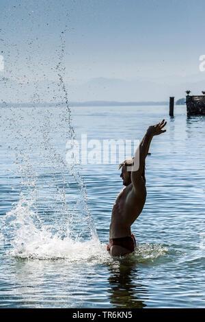 Jeune homme en rouge la baignade dans le Lac de Starnberg éclabloussures, Germany Banque D'Images