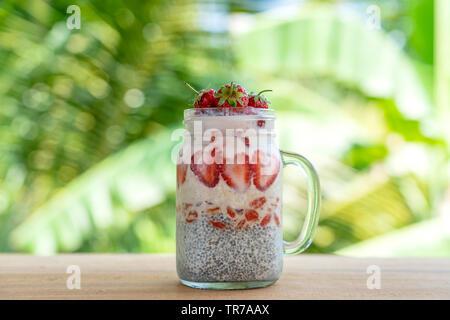 Le lait d'Amande pudding de chia rouges frais avec les fraises, les baies de goji et flocons d'avoine dans un bocal en verre mug. Matières premières. petit déjeuner végétalien Les graines de Chia et de fr Banque D'Images