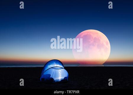 Lune rouge incroyable sur la mer, plage et allumé tente au lever du soleil Banque D'Images