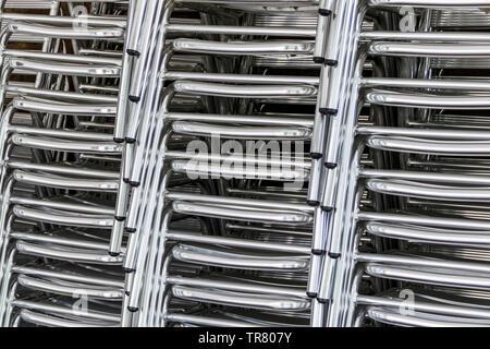Close-up de trois piles de chaises tubulaires en aluminium brillant Banque D'Images