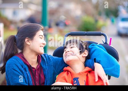 Grande soeur Biracial étreindre amoureusement mobilité petit frère dans wheelchairoutdoors, smiling Banque D'Images