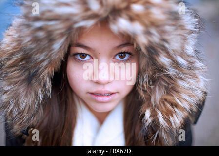 Portrait d'une belle jeune fille asiatique mixte portant une parka jacket coering sa tête en hiver Banque D'Images