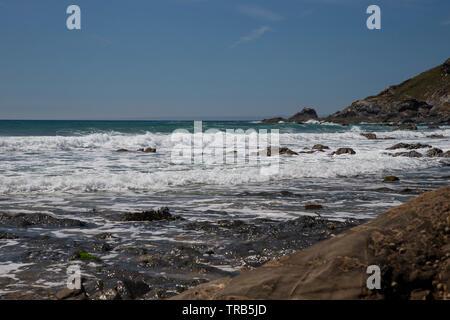 Vue sur l'Océan Atlantique comme la mer échoués sur une des petites criques de la côte de la péninsule du Lézard en Cornouailles, à l'ouest de l'Angleterre, Royaume-Uni Banque D'Images