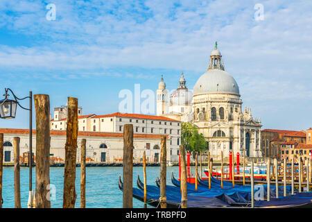 Belle vue sur le Grand Canal avec Basilique historique di Santa Maria della Salute en arrière-plan et gondoles sur une journée ensoleillée à Venise, Italie