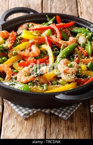 Sauté asiatique délicieux de crevettes aux légumes, close-up de sésame dans une poêle sur la table. vertical Banque D'Images