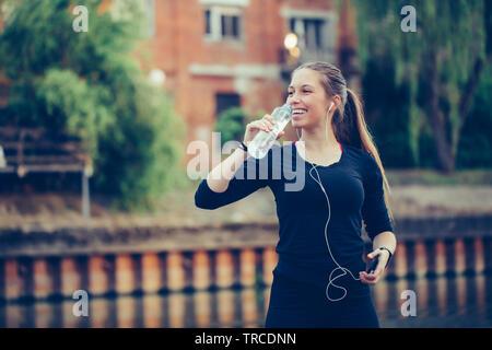 Coureuse debout près de la rivière tenant une bouteille d'eau. Femme de remise en forme en faisant une pause après l'exécution de l'entraînement.