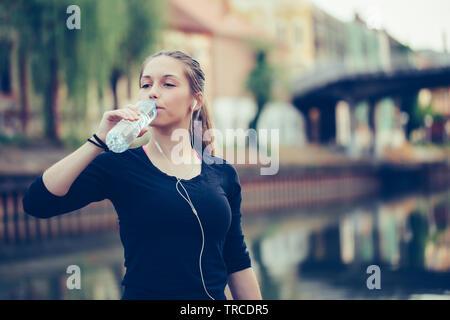 Belle femme athlète remise en forme de l'eau potable après l'exercice d'entraînement.