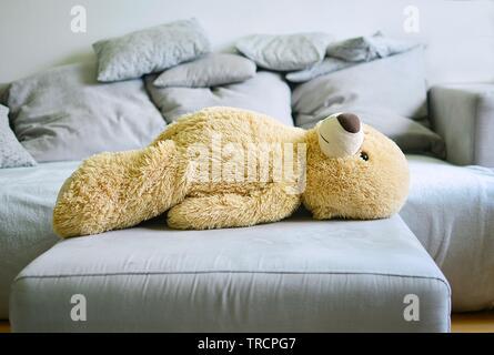 Le grand ours se trouve sur un canapé