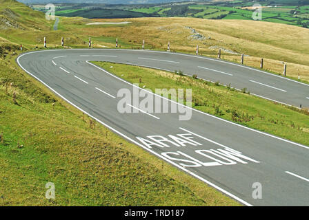 Route de campagne, des marquages de sécurité bilingue ralentir sur l'autoroute des panneaux d'avertissement de l'aire de virage en épingle en route dans la campagne galloise Brecon Beacons au Pays de Galles UK Banque D'Images