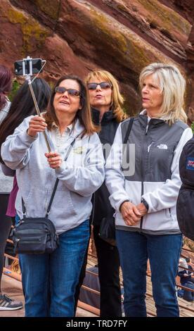 Utiliser une femme trois stick selfies pour prendre leur photo de groupe avec téléphone cellulaire à Red Rocks Park Amphitheater près de Colorado Morrison nous. Photo prise en mai. Banque D'Images