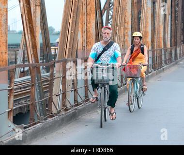 Des couples de la bicyclette ensemble sur des voies de chemin de fer menant au pont Long Bien, il est conçu par Gustave Eiffel à Hanoi, Vietnam Banque D'Images