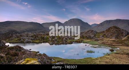La chaude lumière du matin sur la montagne de Lakeland Grand Gable reflétant en Tarn innommé