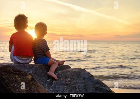 Deux garçons assis sur le rock à la plage en regardant le coucher du soleil magnifique, l'Australie du Sud Banque D'Images